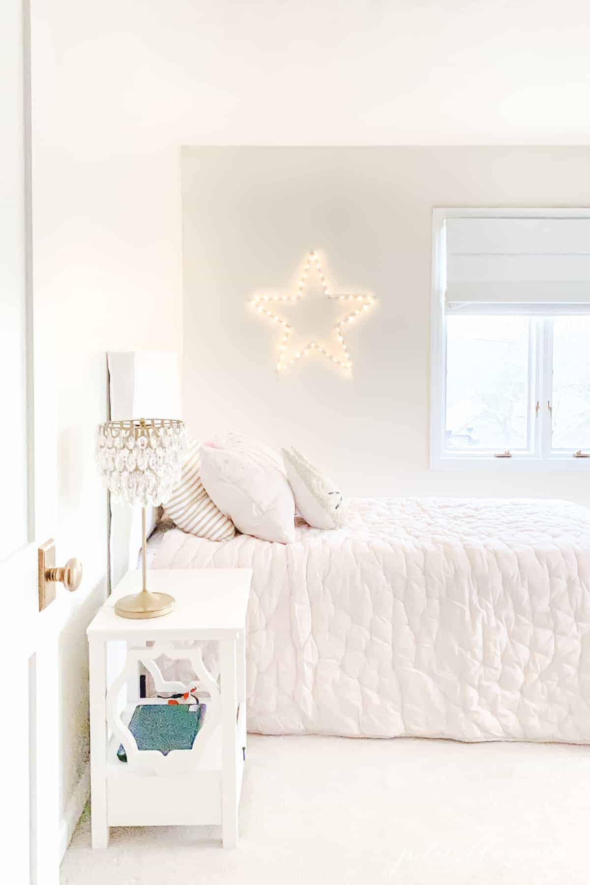 cream bedroom with pink quilt chandelier lamp and star light