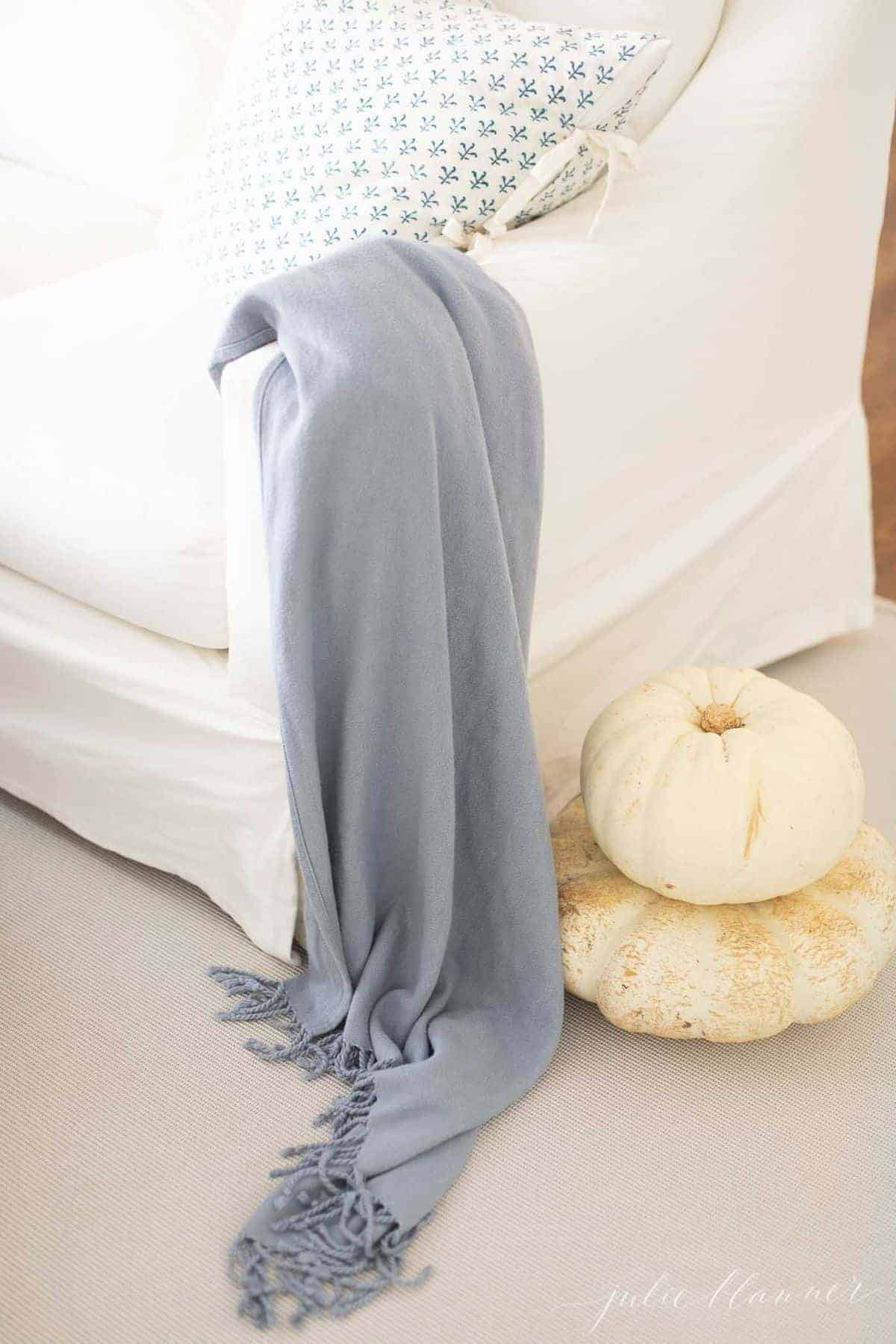 A white slipcovered pottery barn sofa with a blue blanket throw over the arm and two white pumpkins on the floor.