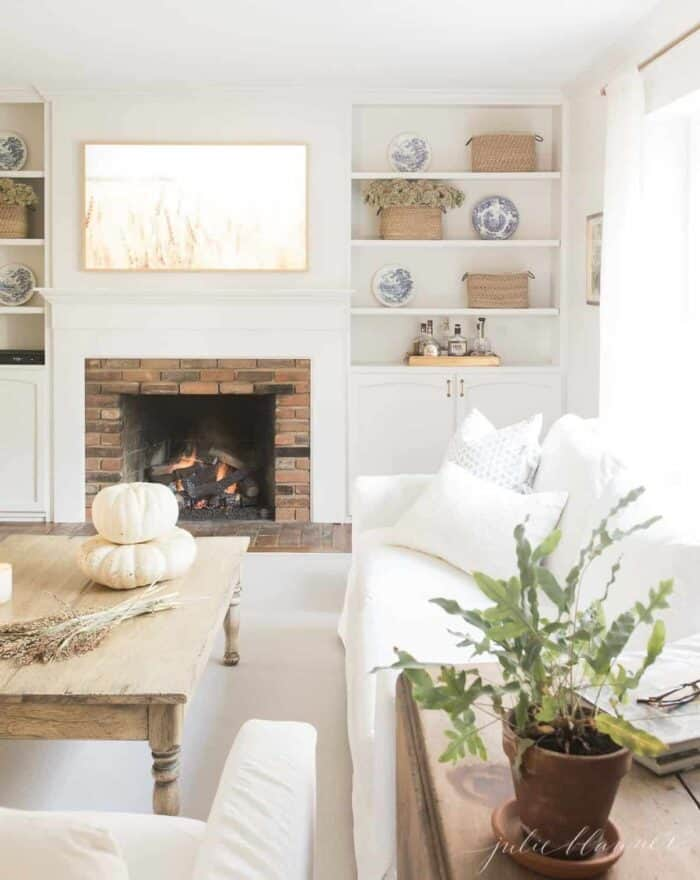 A white living room with two white slipcovered Pottery Barn couches.