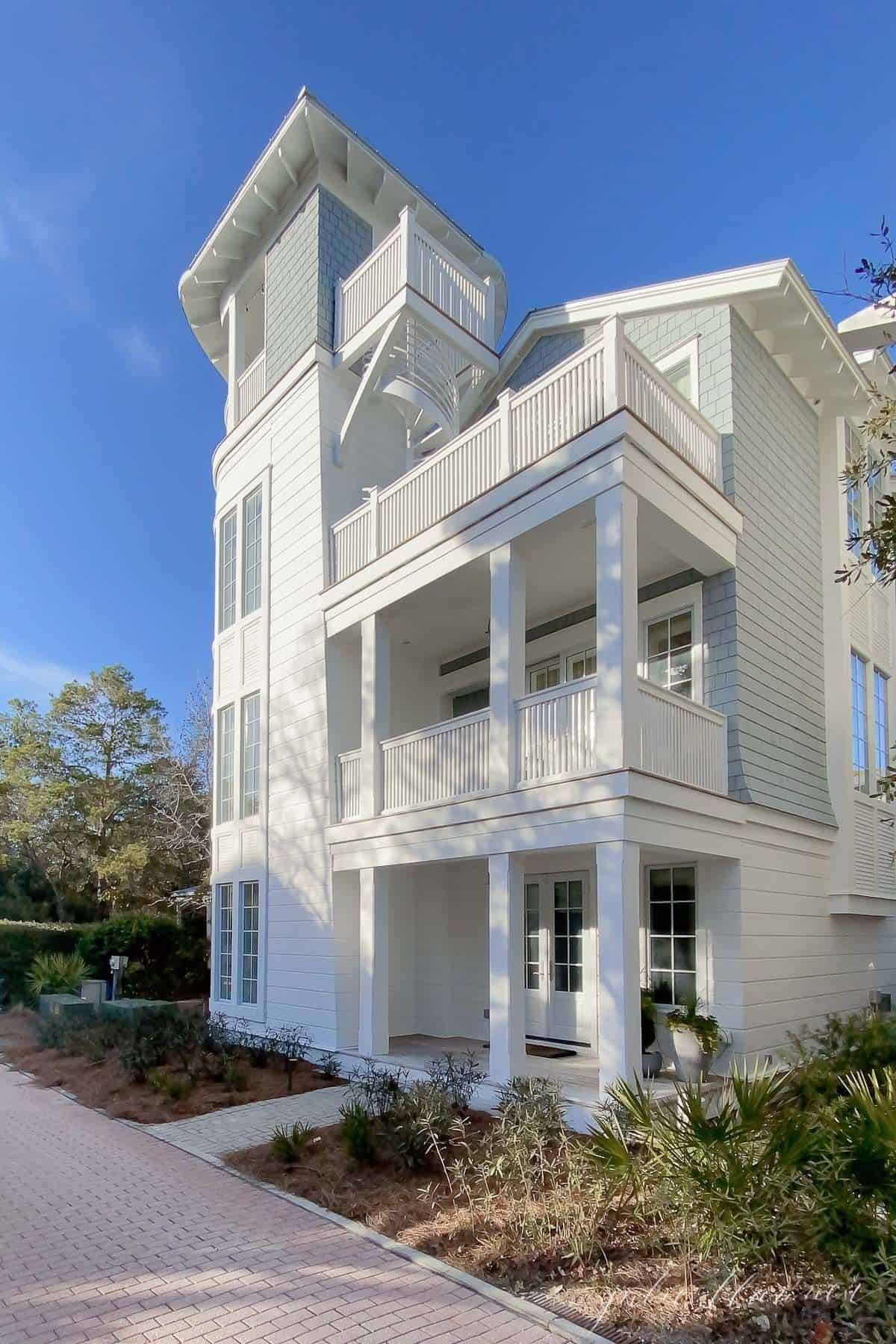 A charming three story white beach house with a white front porch in Seaside Florida