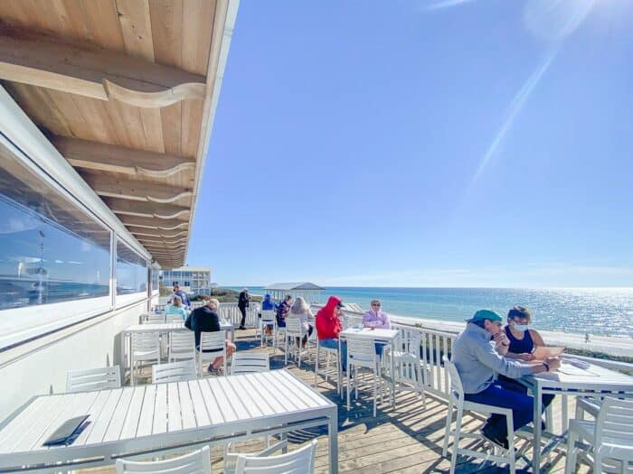 A pretty restaurant patio on the beach in Seaside Florida, diners at small tables along patio.