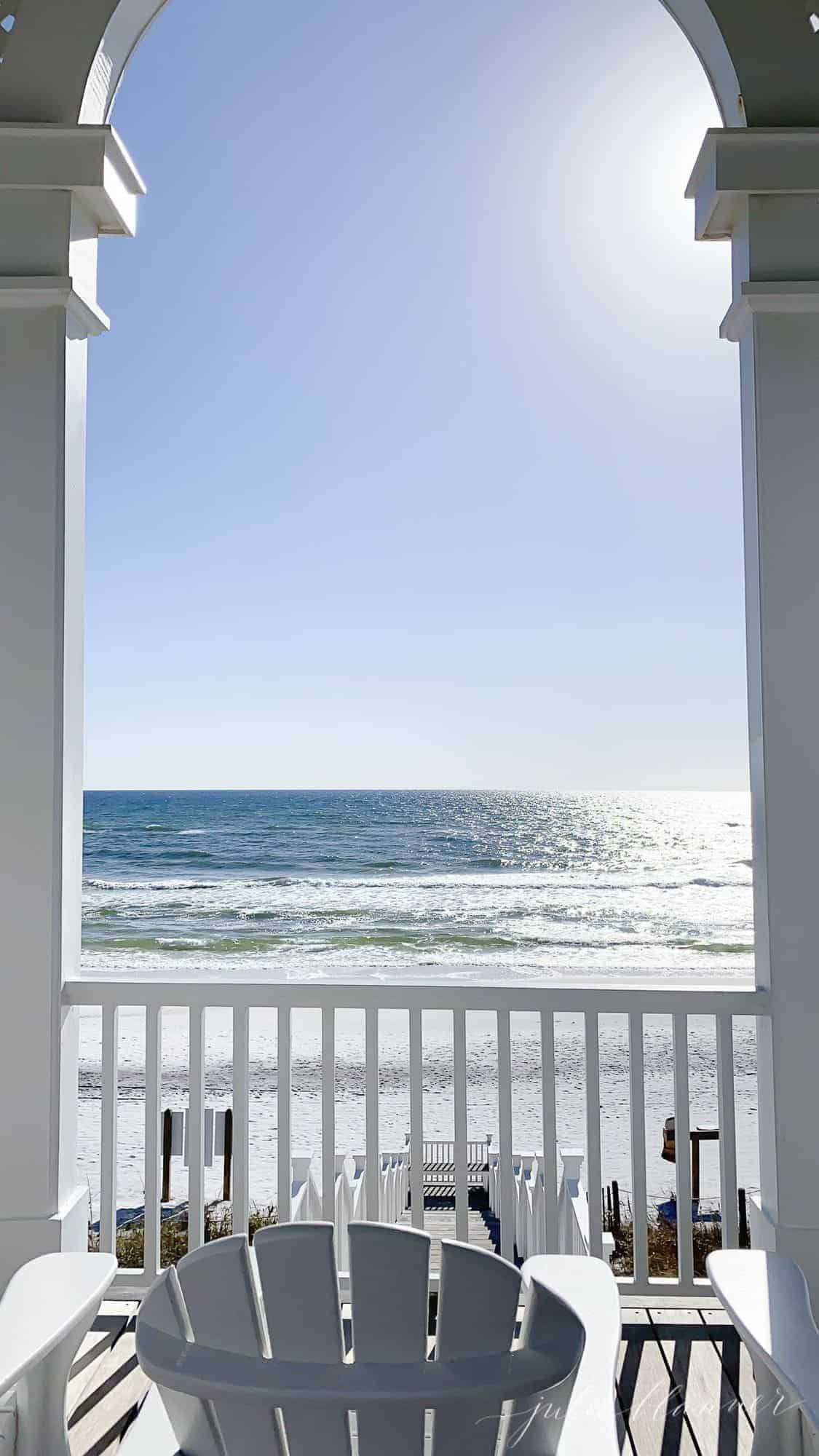 A beach scene looking through a pavilion with seating.