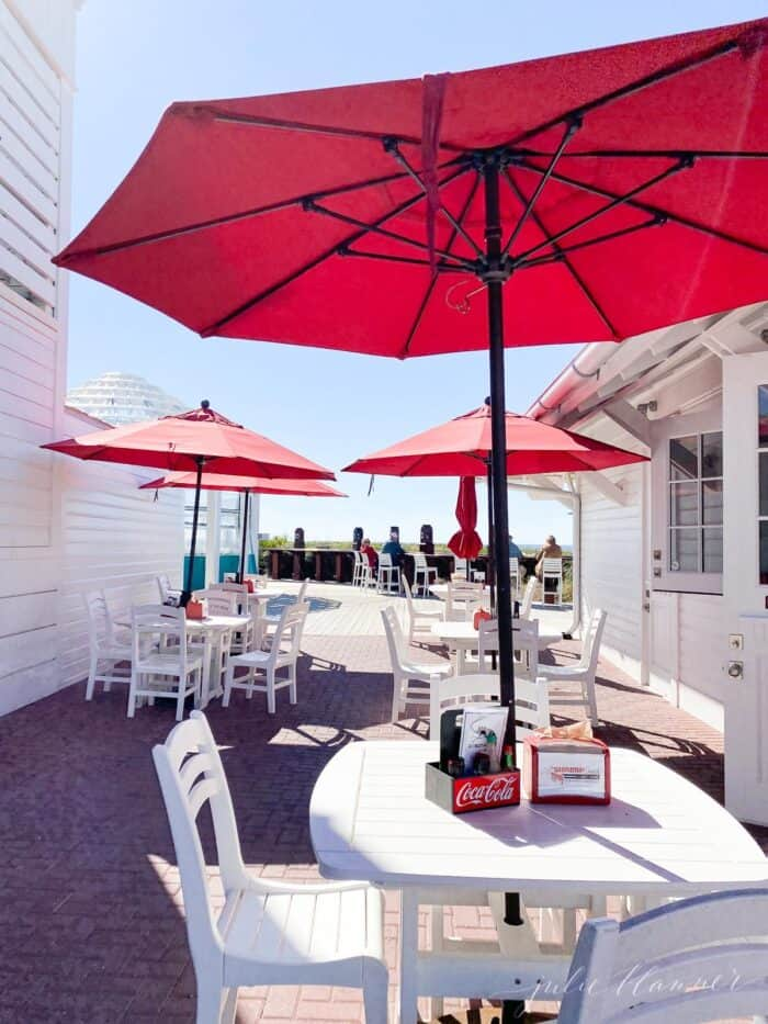 Red umbrellas on white patio tables and chairs on a restaurant patio in Seaside Florida.