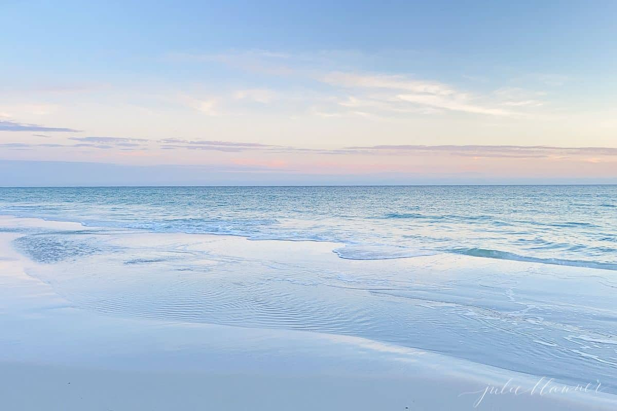 A blue and pale pink beach sunset scene