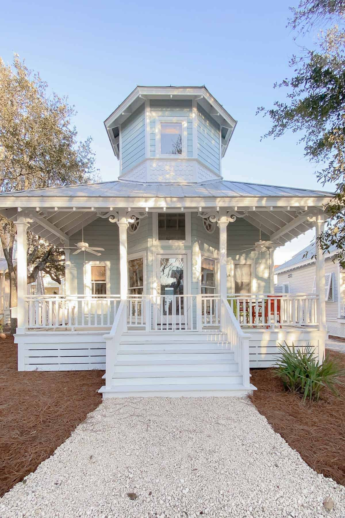 A charming pale blue beach house with a white front porch in Seaside Florida