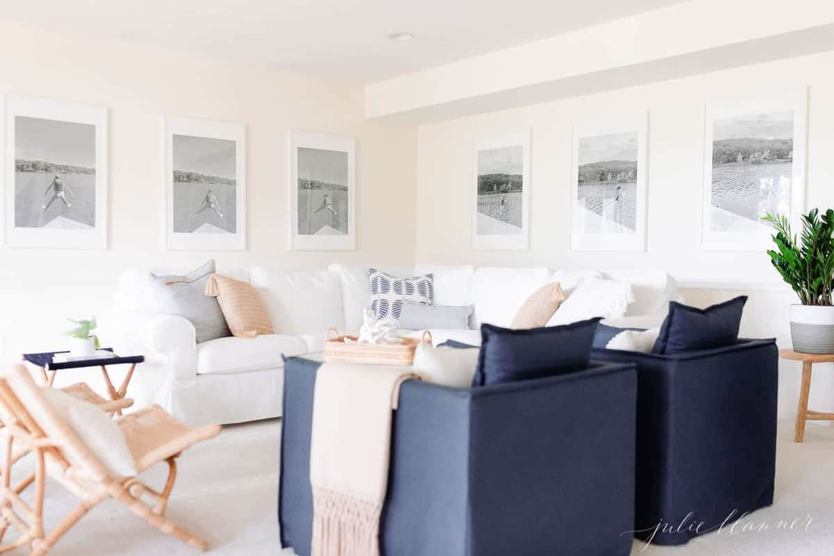 A modern white living room with large black and white photos on the wall, a white sectional sofa and navy blue chairs.