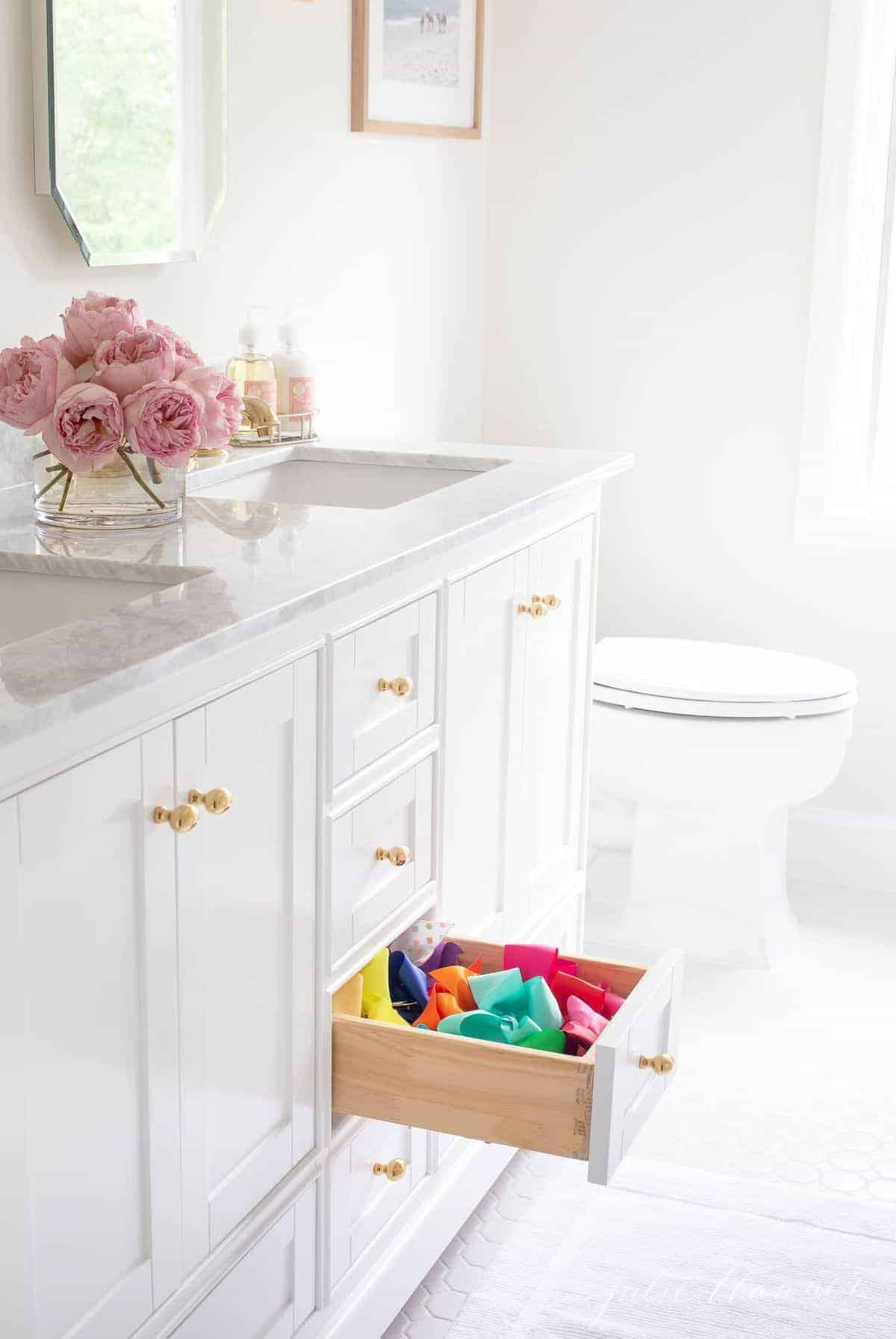 A shaker style bathroom vanity cabinet with gold knobs, one drawer pulled open to showcase storage.