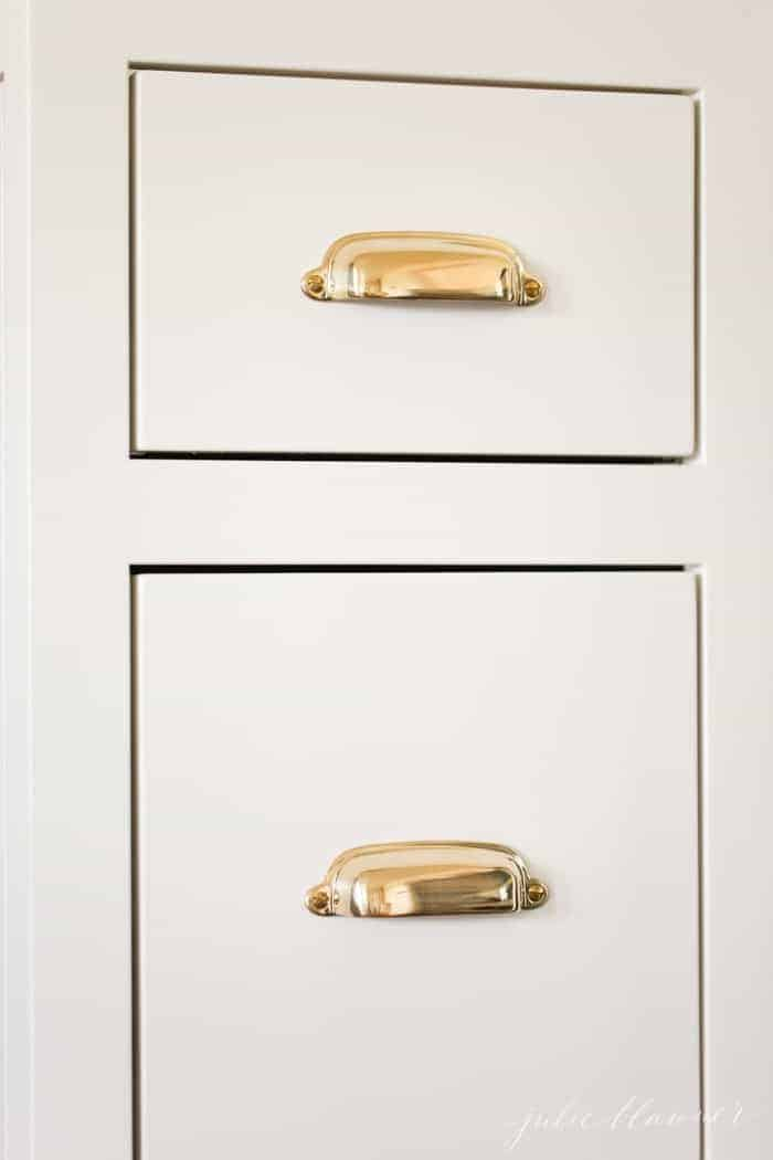Brass cabinet pulls on cream inset kitchen cabinets.