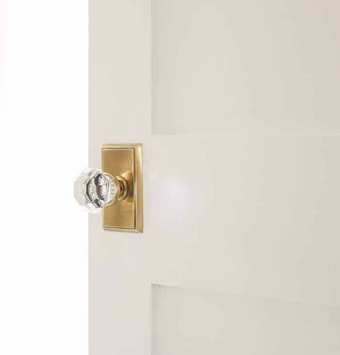 A white Shaker door with a brass doorknob, opening into a bedroom.