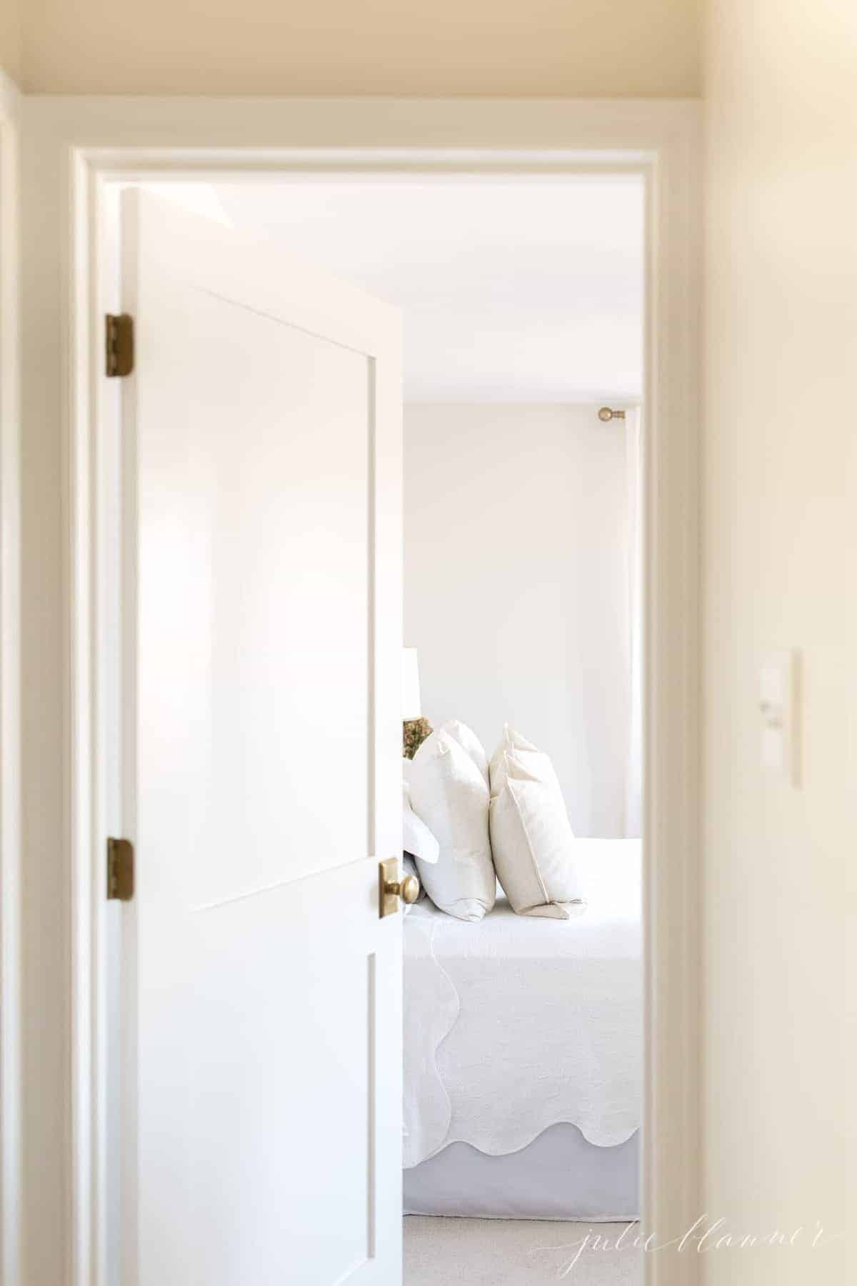 A white Shaker interior door with a brass doorknob, opening into a bedroom.