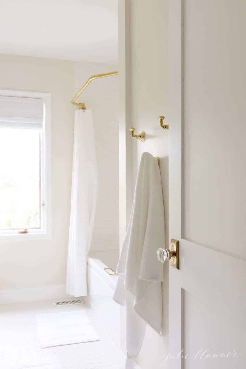 A white Shaker style door with a brass doorknob, opening into a bathroom.