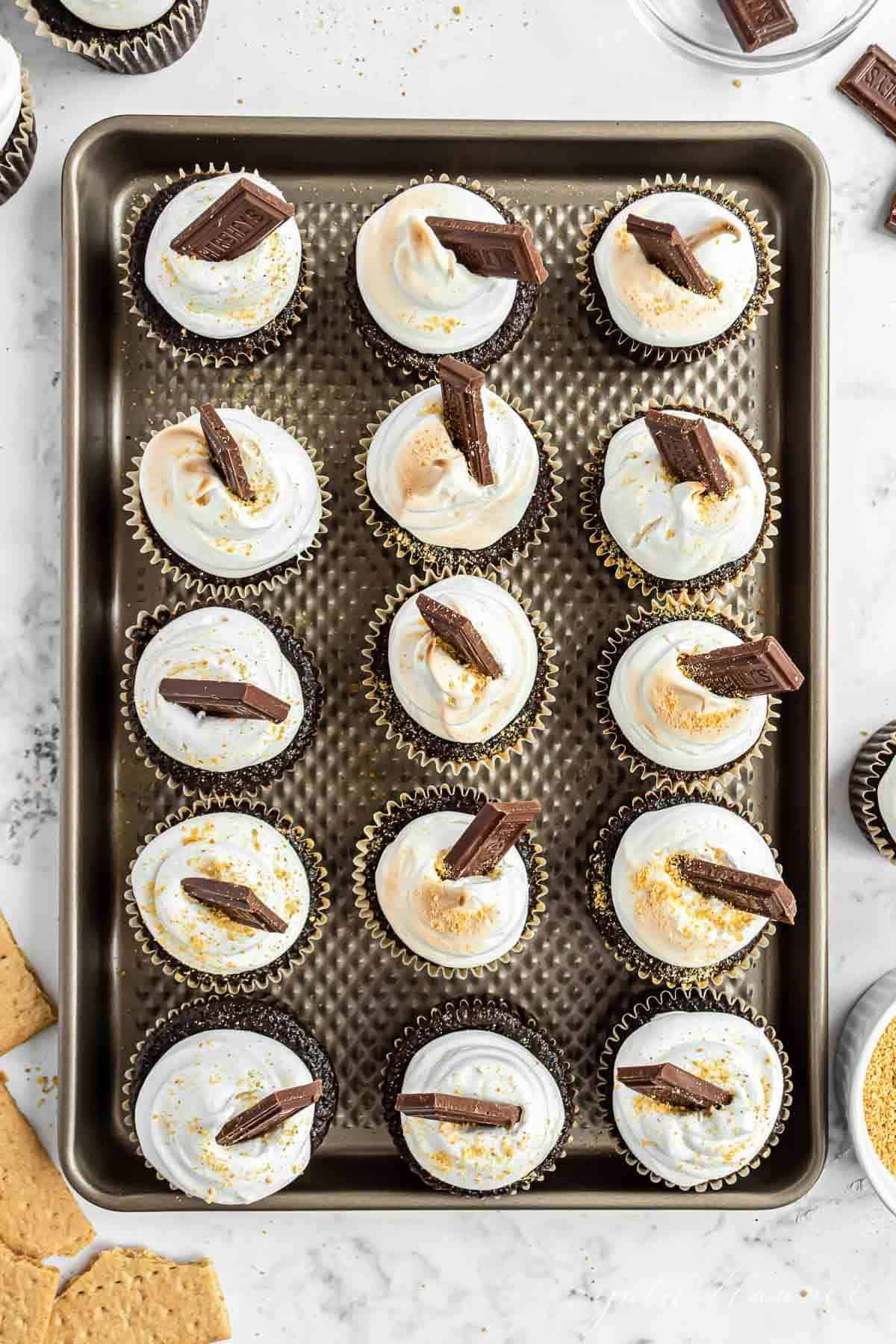 Homemade smores cupcakes on a baking sheet, lined up and topped with marshmallow frosting and a piece of Hersheys bar.