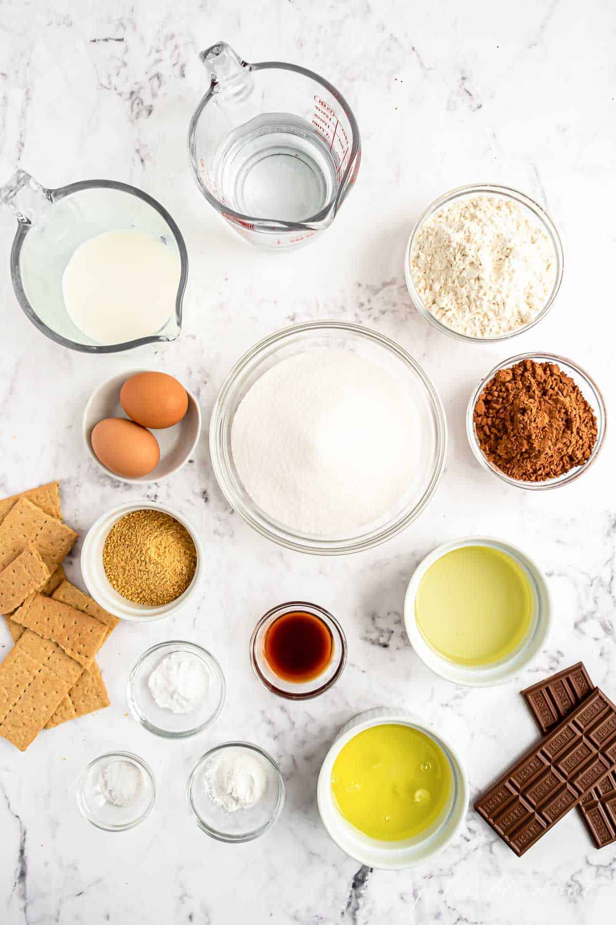 All the ingredients for smores cupcakes laid out on a white countertop.