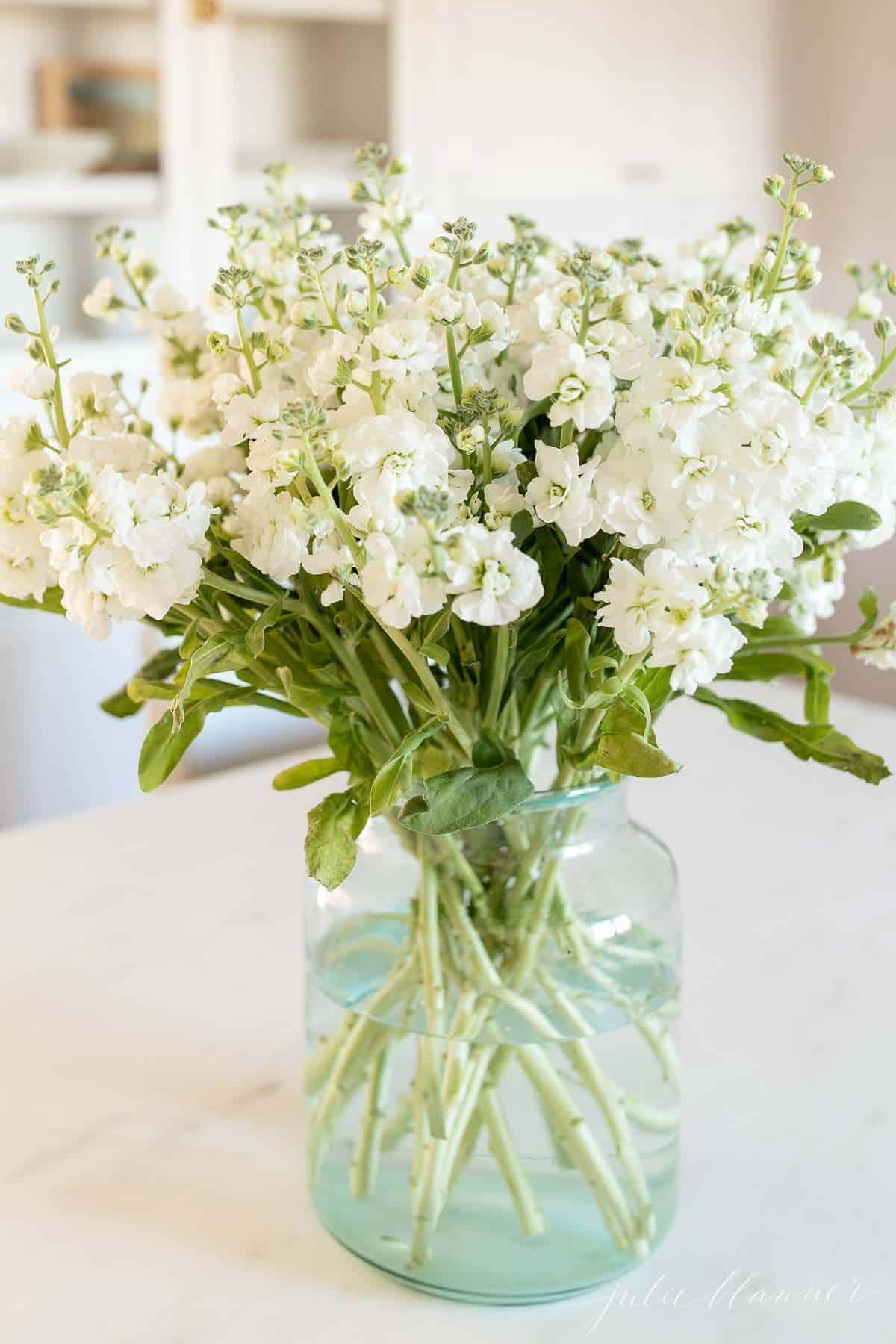 Um arranjo de flores brancas em um vaso de vidro transparente sobre uma superfície de mármore.