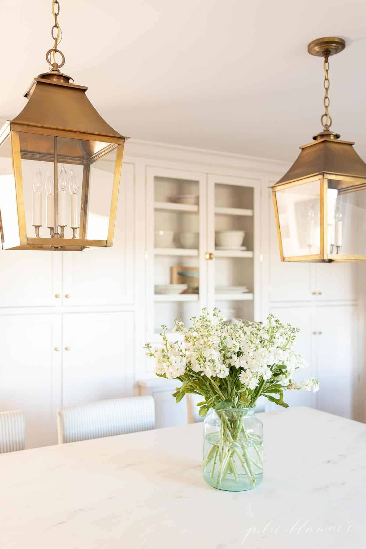 A white kitchen with brass lanterns and marble countertops, with a stock flower arrangement on the island.