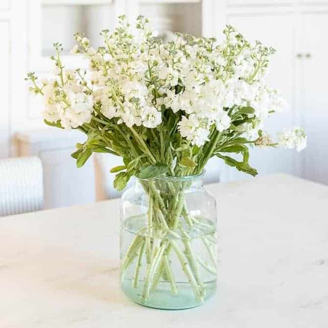 A white stock flower arrangement in a clear glass vase on a marble surface.