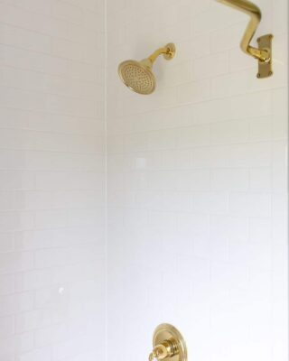 A white subway tile shower with brass hardware.