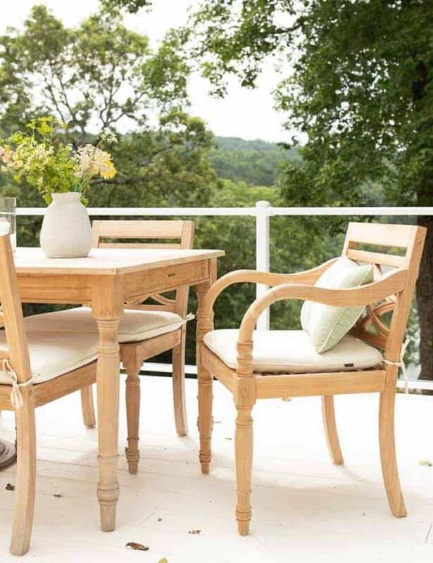 Teak wood furniture dining set on a white patio with a glass railing.