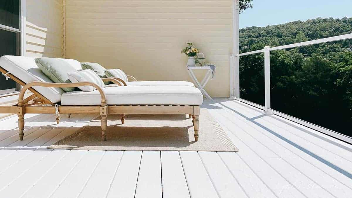 Teak patio furniture chaise lounges on a white deck.