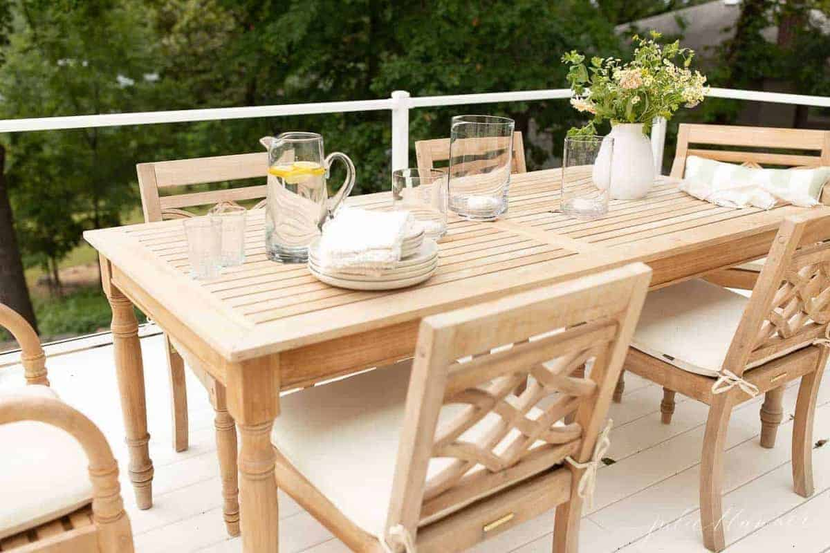 Teak outdoor furniture dining set on a white patio with a glass railing.