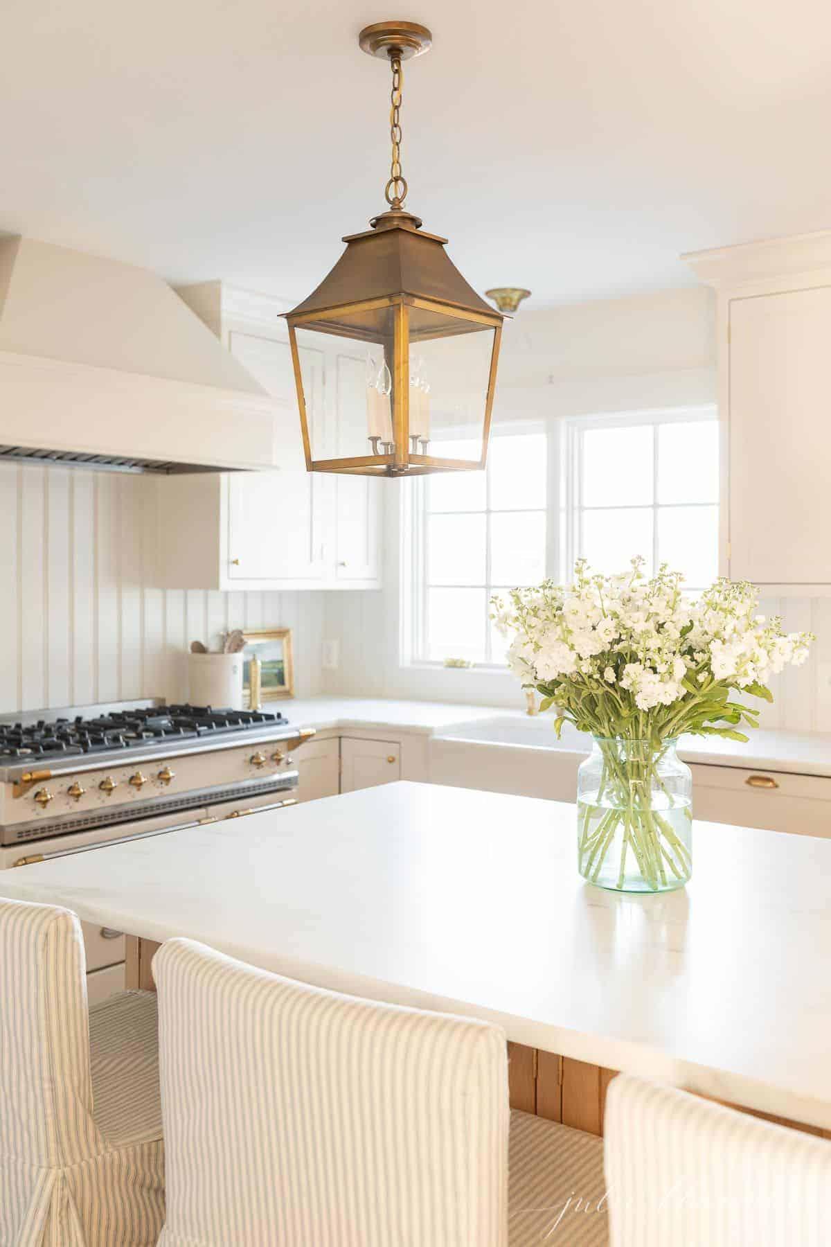 Uma cozinha branca com lanternas de latão e bancadas de mármore, com um estoque de flores na ilha.