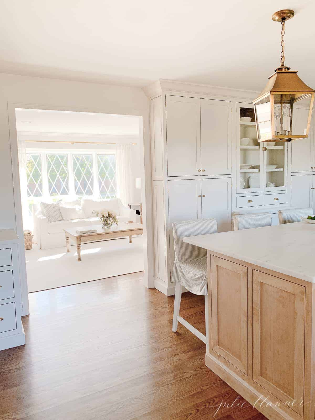A kitchen island with a brass lantern hanging above.