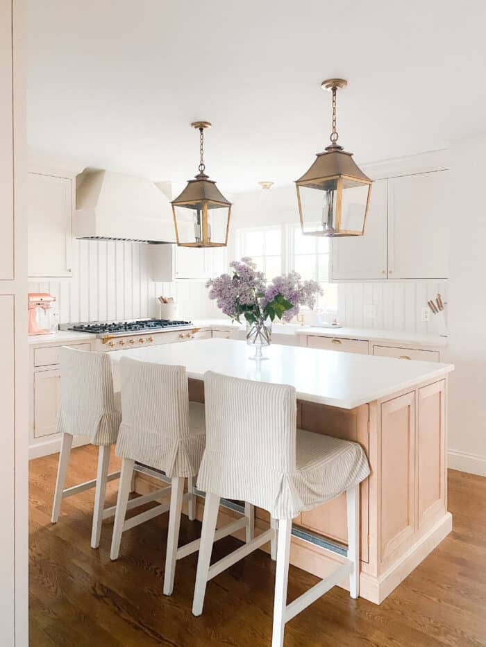 brass lanterns over light wood kitchen island in a cream kitchen with Danby marble countertops.
