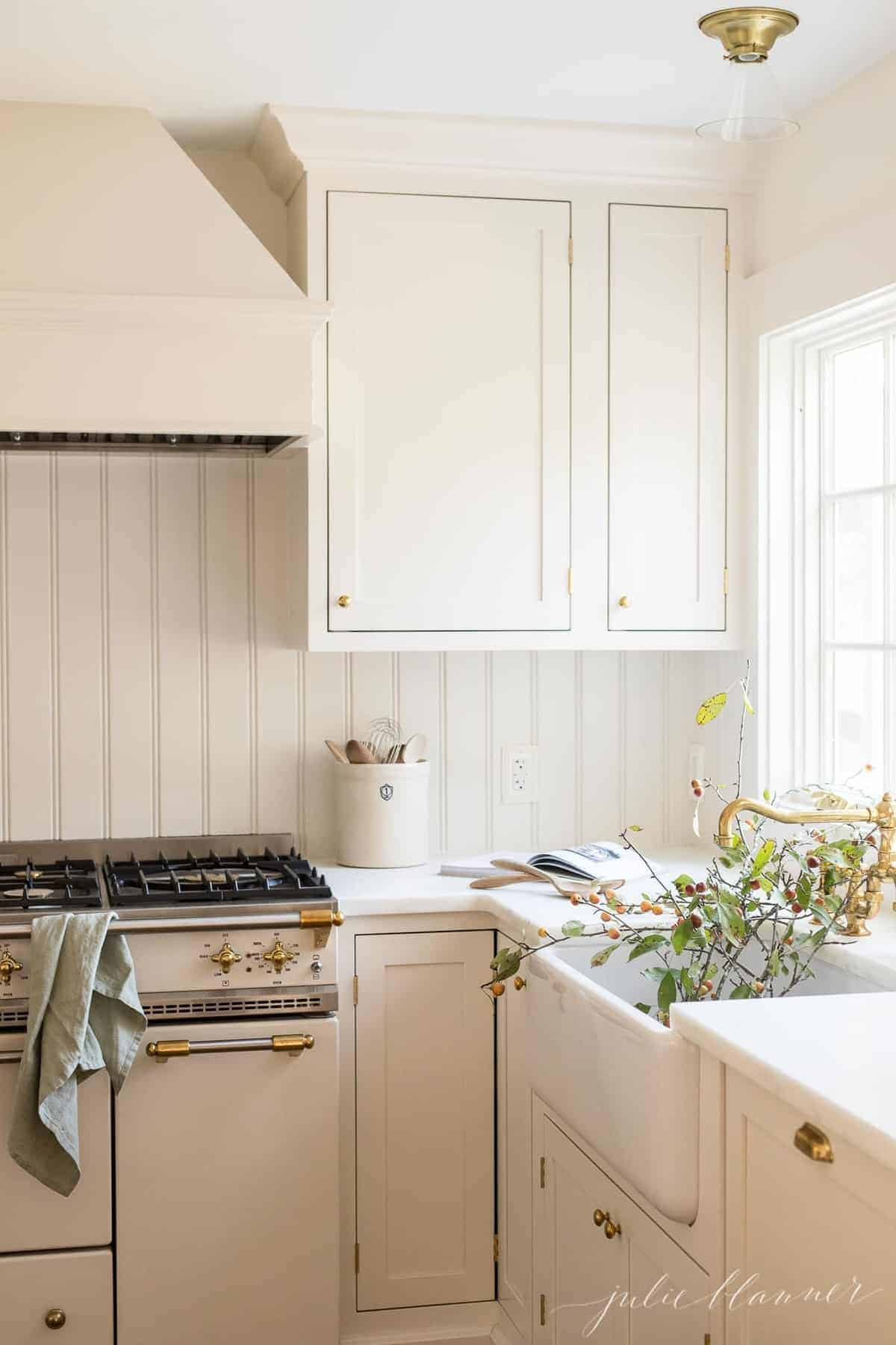 A farmhouse style kitchen with a beadboard backsplash, and cut branches in the farm sink.