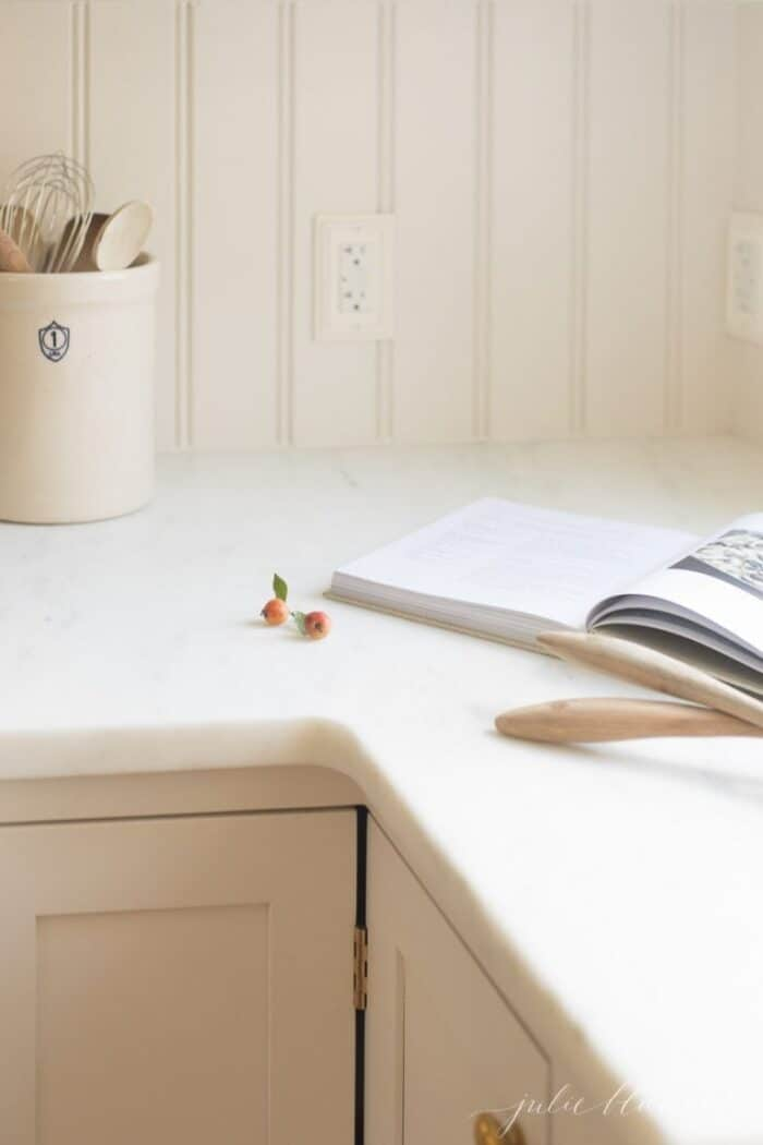 A beadboard backsplash in a cream kitchen, with marble countertops with an eased edge. and white marble countertops, with a cookbook open on the counter.