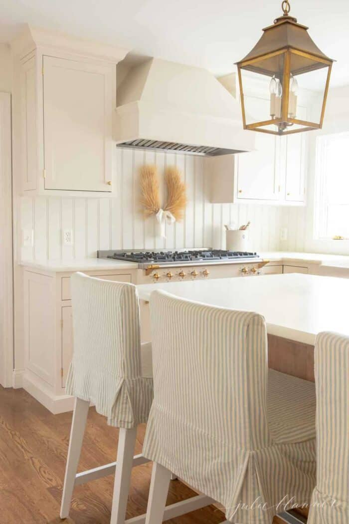 A white and wood kitchen with an marble eased edge countertop