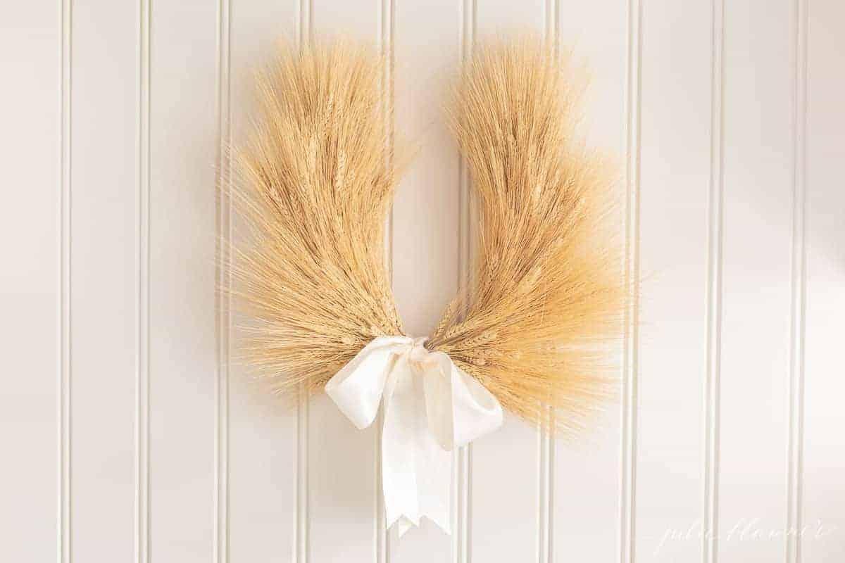 A wheat wreath on a beadboard background.
