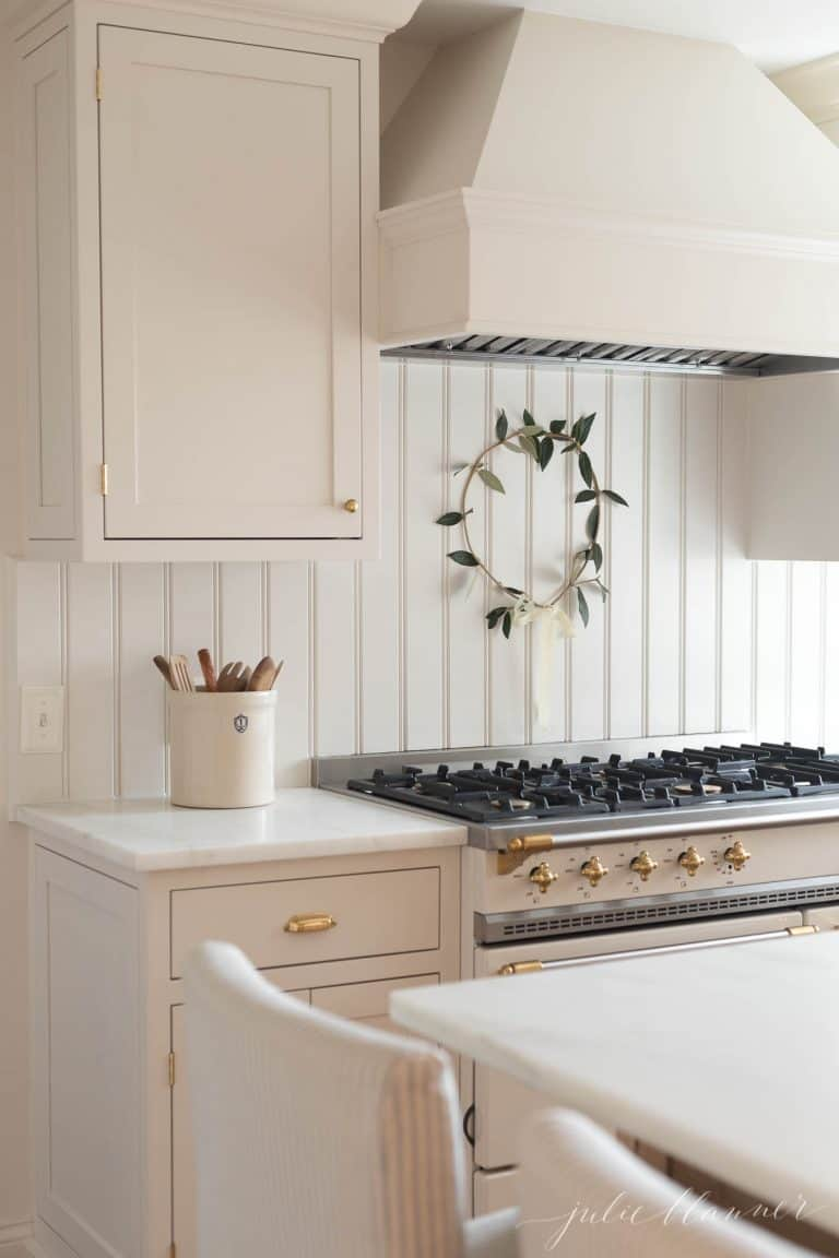 A white kitchen with a small wreath over the range.