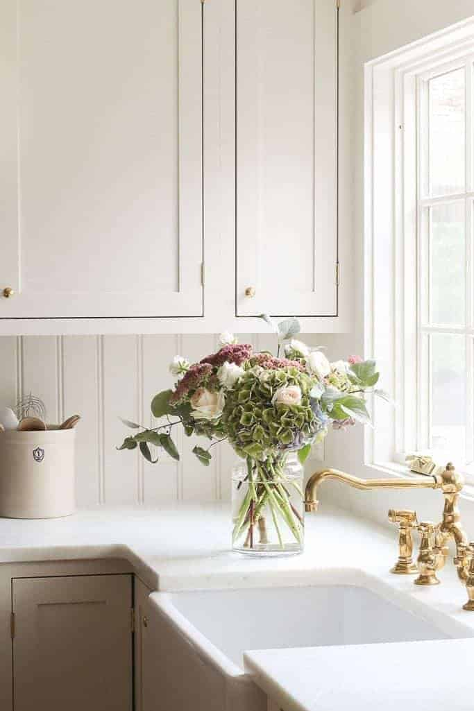 A farmhouse style kitchen with a beadboard backsplash, and cut flowers in a vase by the sink.
