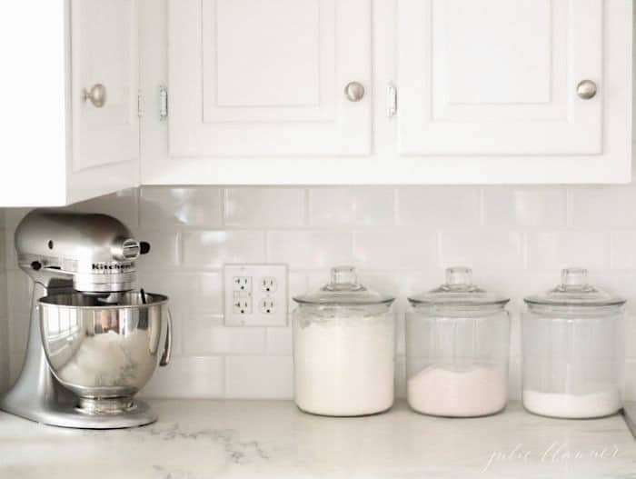 A white kitchen with marble countertops, a stand mixer and glass canisters of baking supplies.