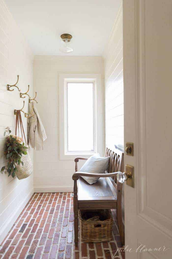 A white mudroom with horizontal paneling, brass hooks and a wooden bench.