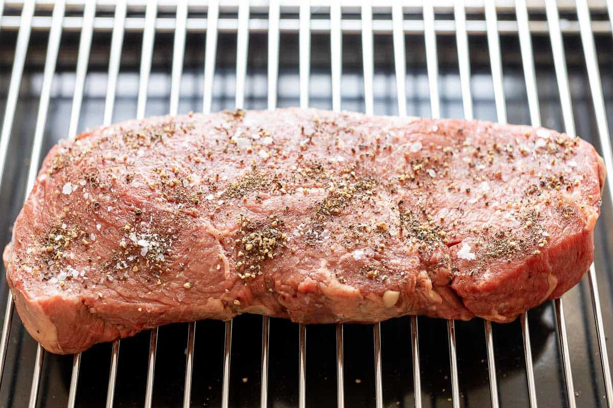 A large steak on a broiling rack, topped with seasoning for a broiled steak tutorial.
