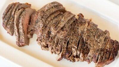 Bife grelhado em uma travessa branca, cortado em pedaços finos.
