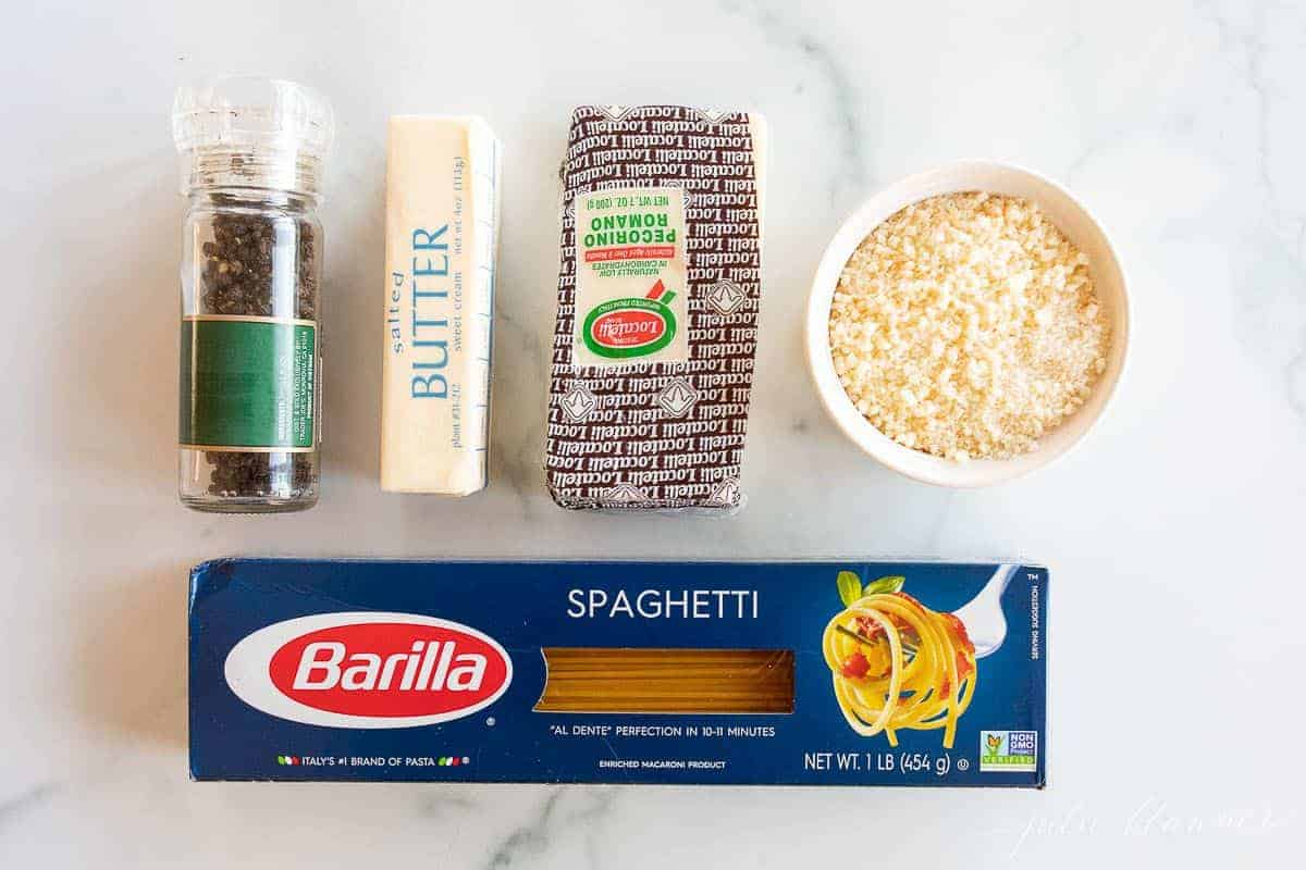 Ingredients for cacio e pepe laid out on a marble surface.