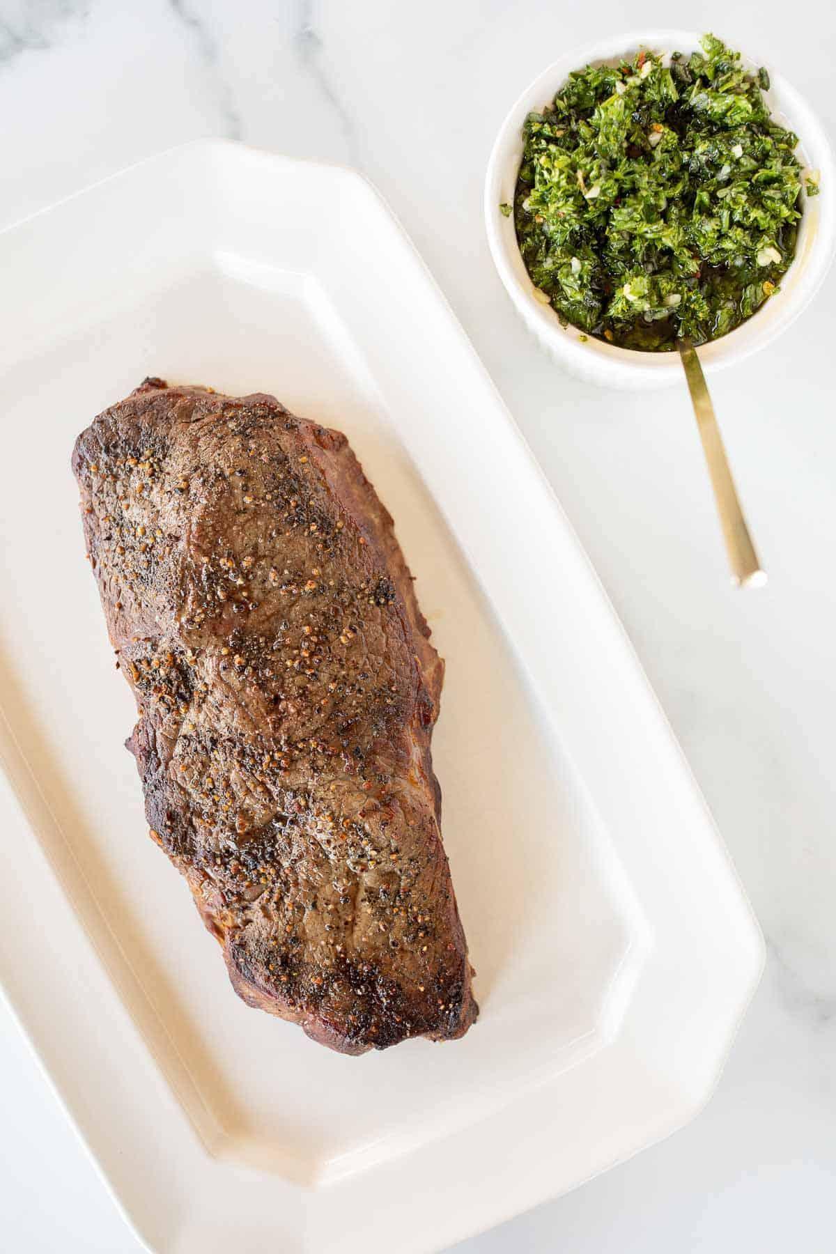 Um bife em uma travessa branca, tigela de molho chimichurri ao lado com uma colher de ouro.