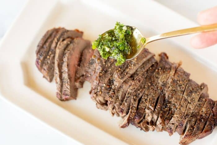 A platter of sliced steak, with a gold spoon coming in full of chimichurri sauce.