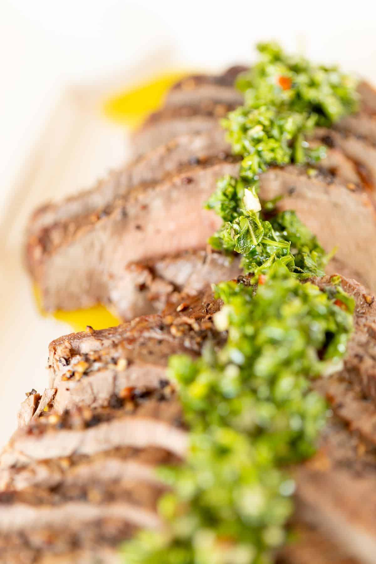 Sliced steak on a white platter, topped with chimichurri.