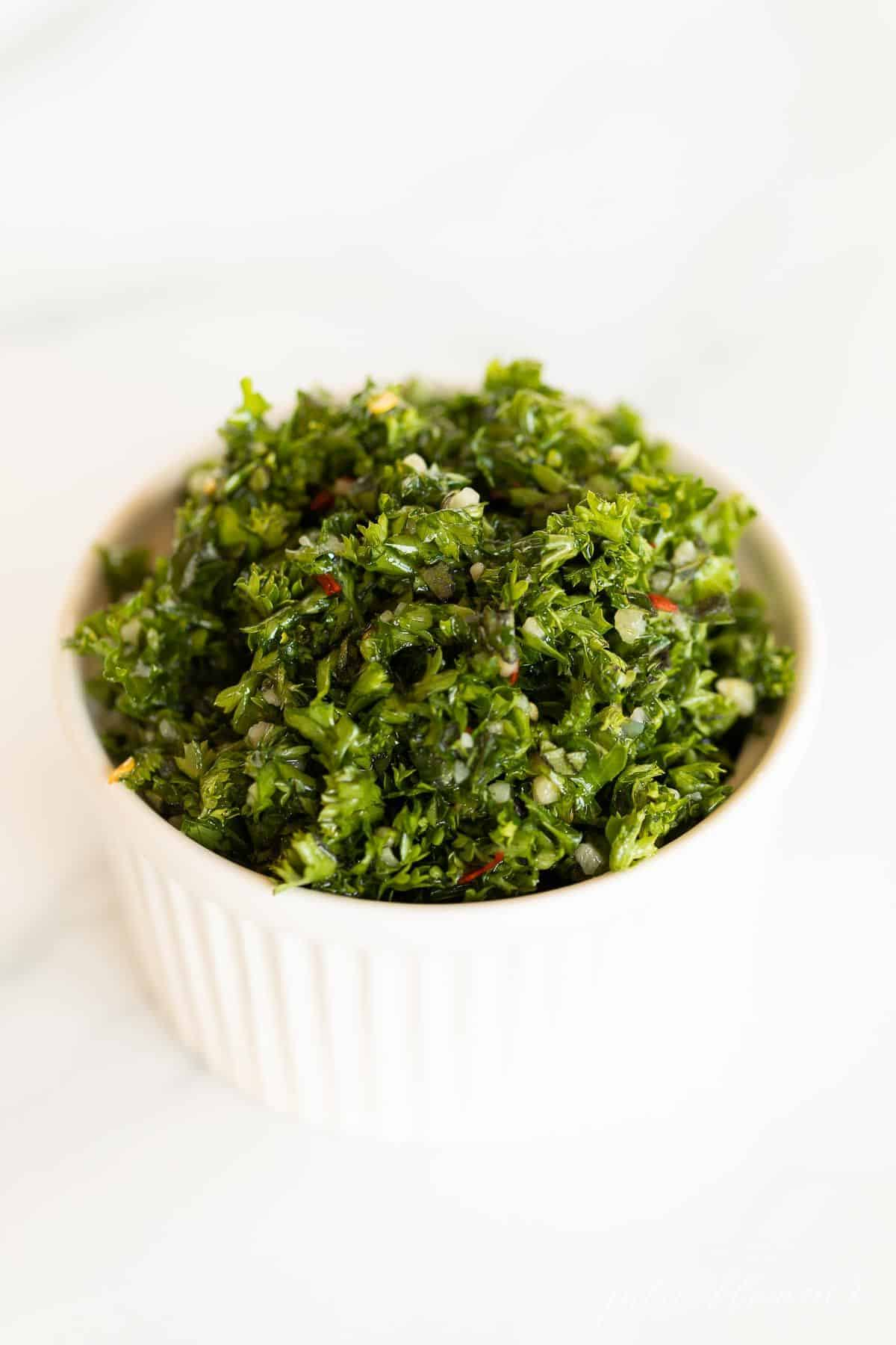 A white ramekin full of chimichurri on a marble surface.