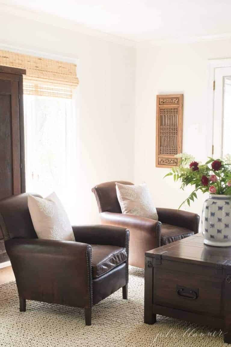 A family room with leather chairs and dark wood furniture, with a cream eggshell paint on the walls.