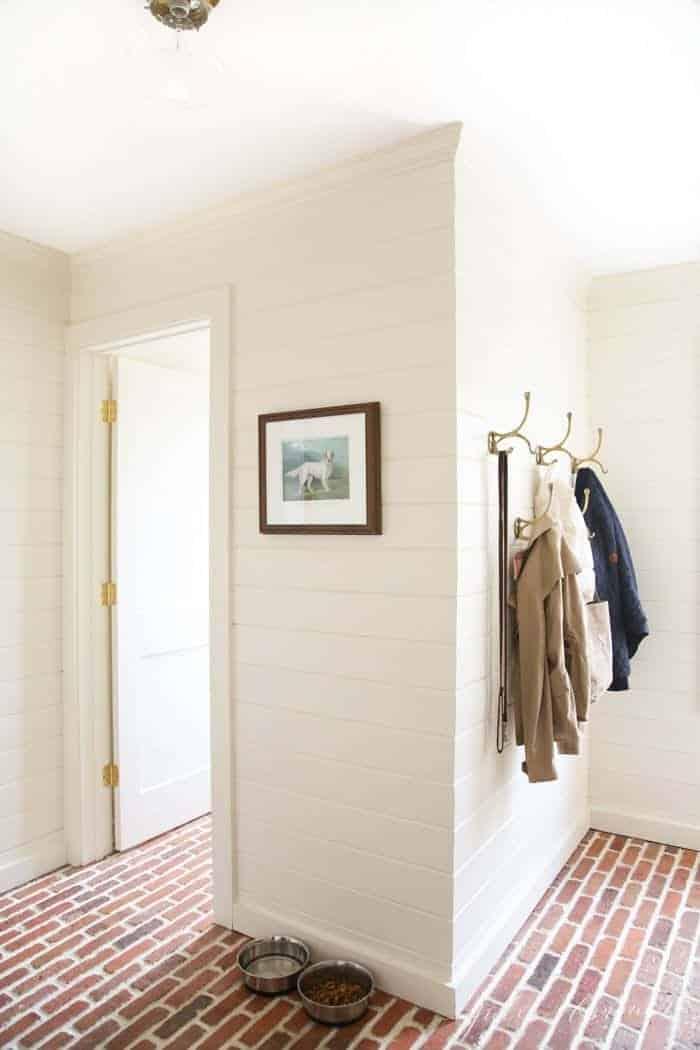 cream mudroom with brick floors, art and coats on hooks