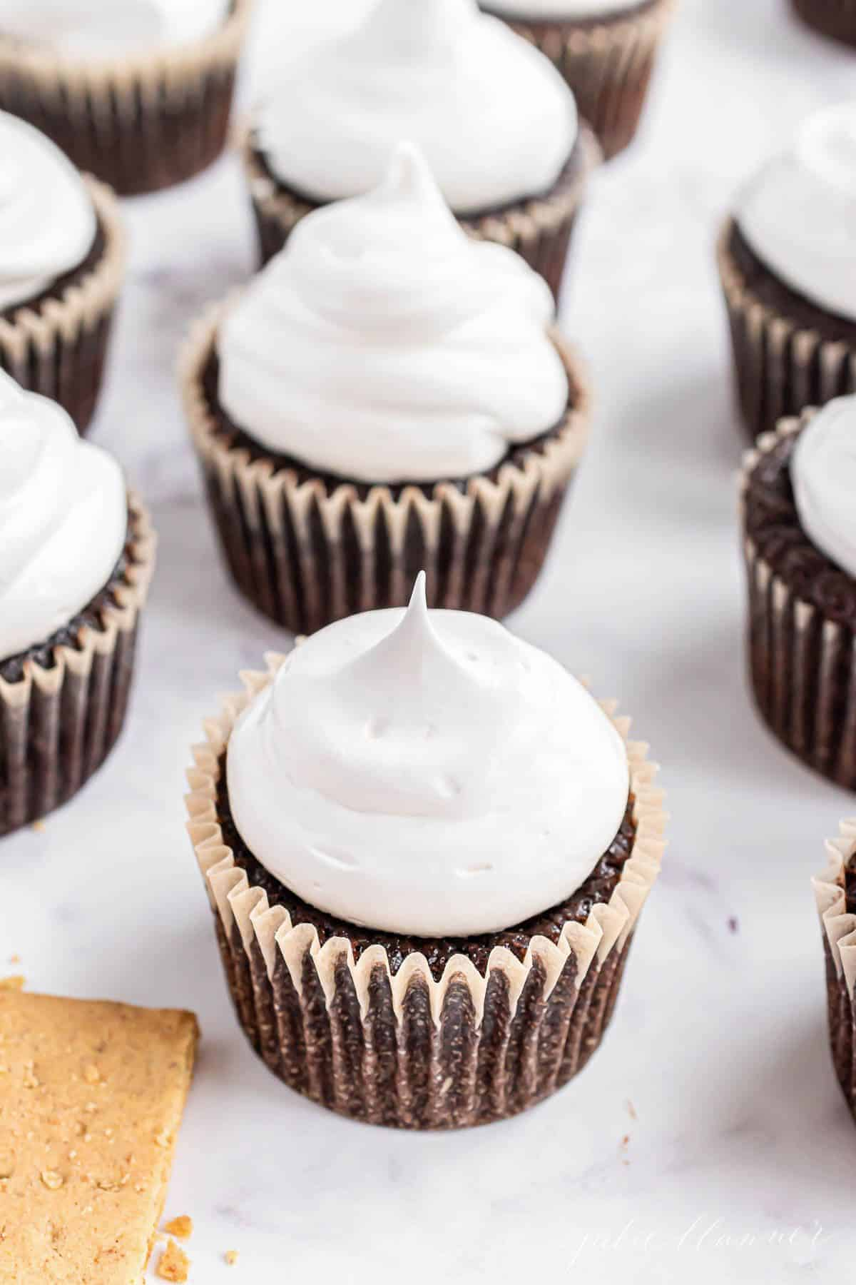Chocolate cupcakes on a white marble surface, topped with marshmallow frosting.