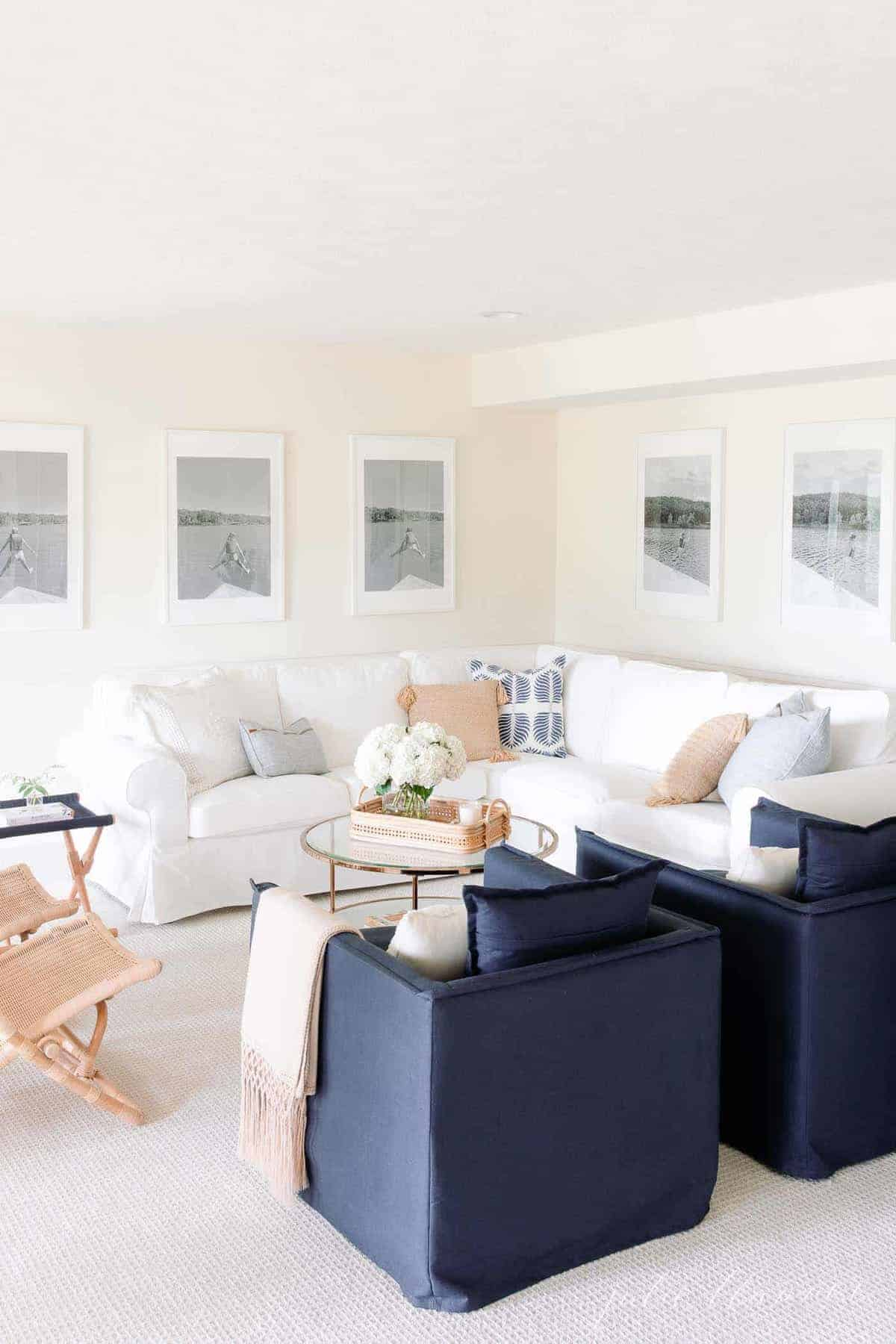 A living room with white furniture with a cream eggshell paint on the walls.