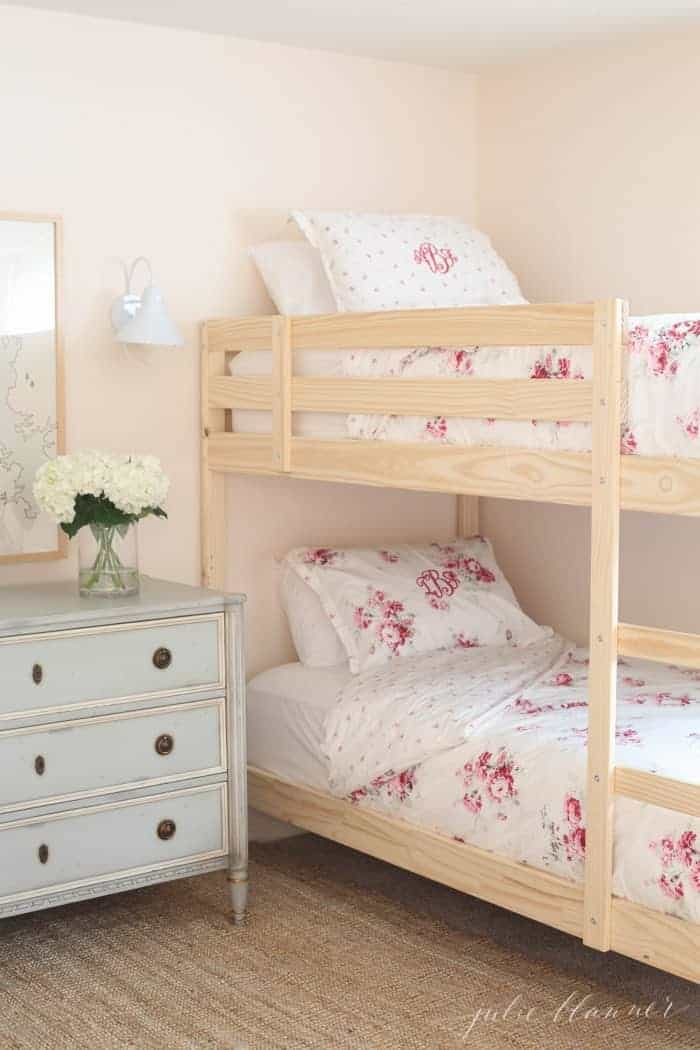 A little girls' bedroom with wooden bunk beds, floral bedding and pale pink eggshell paint on the walls.