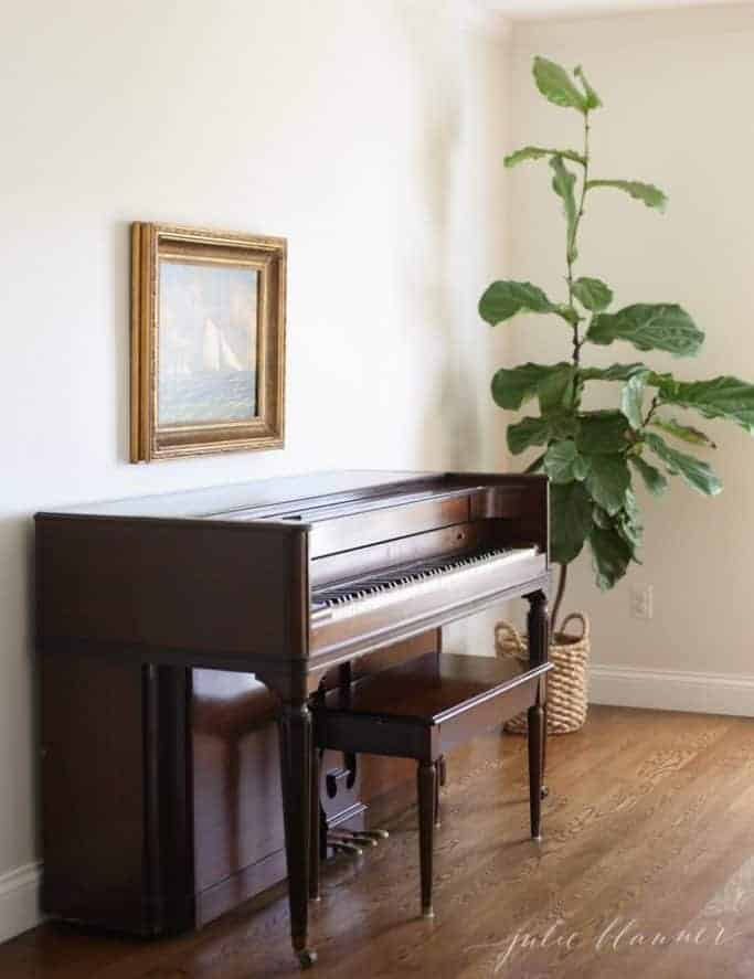 piano with painting above and fiddle leaf fig to side