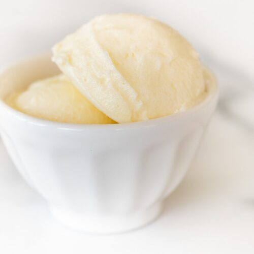 A small white bowl full of sweet butter on a marble counter top.