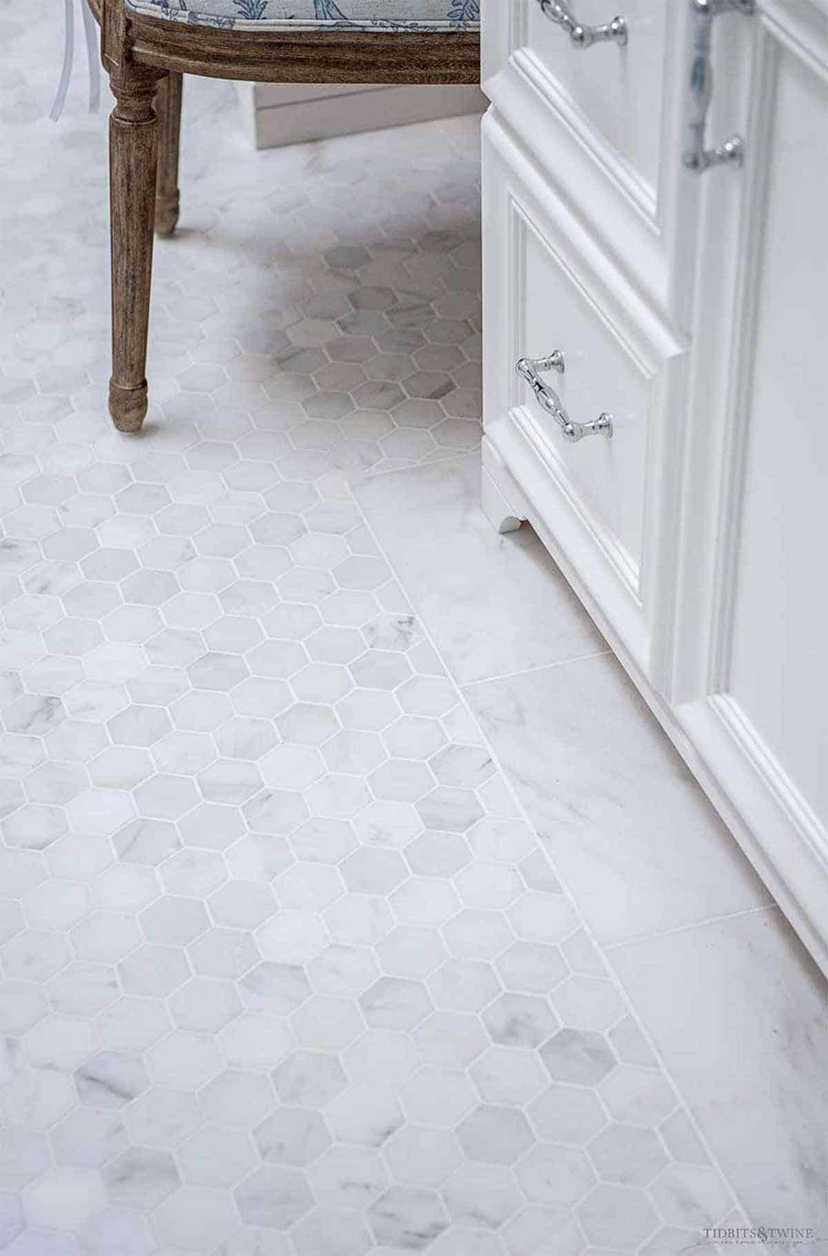 Pequeno ladrilho hexagonal no chão de uma casa de banho, base de toucador branca à direita.